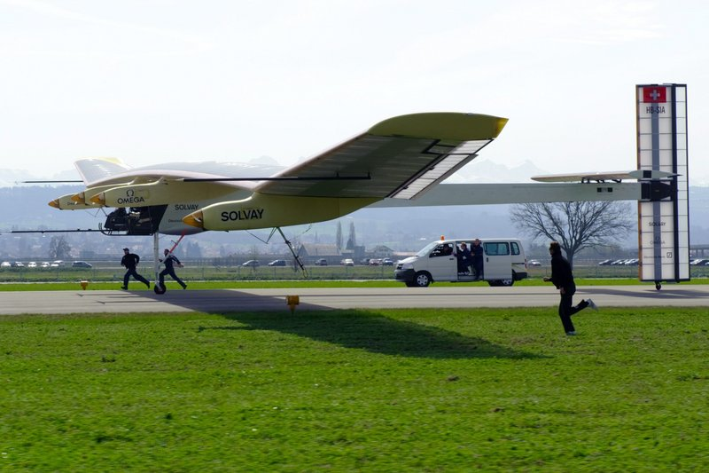 """The solar powered aircraft """"Solar Impulse,"""" with test pilot Markus Scherdel, lands after its maiden flight at the military airport in Payerne, Switzerland, on Wednesday. The prototype, with the wingspan of a Boeing 747 and the weight of a small car, proved in a 90-minute test that it can keep a straight trajectory."""