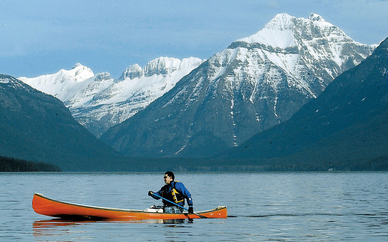 Jon Crandall of Coram, Mont., paddles his canoe across Lake McDonald in Glacier National Park, Mont. Scientists said Wednesday that the park has lost two more of its namesake moving ice fields to climate change, which is shrinking the rivers of ice until they halt.