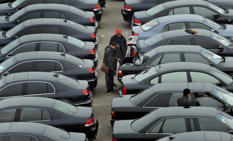 Customers trade used vehicles at an auto market in Shenyang, in northeast China. Passenger car sales in China soared in March.