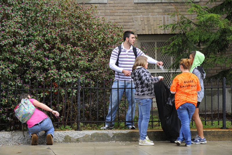 Middle-school kids enrolled in the Jobs for Maine's Graduates program pick up trash around Portland High School on Friday.