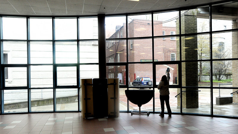 A middle-school student enrolled in the Jobs for Maine's Graduates program washes windows at Portland High Schoolon Friday. About 150 students from around the state participated in community service projects in the citu.