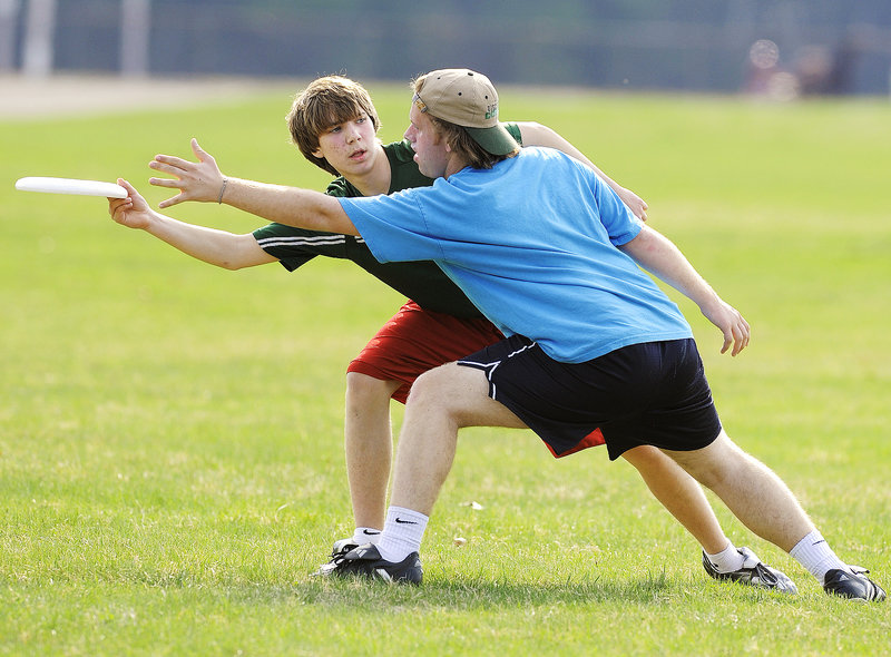 Cyrus Fenderson of Merriconeag, left, tries to work around tight defending by Stephen Webel of Falmouth. Some high school athletes say they are drawn to Ultimate Frisbee for the sport's freewheeling sensibility.