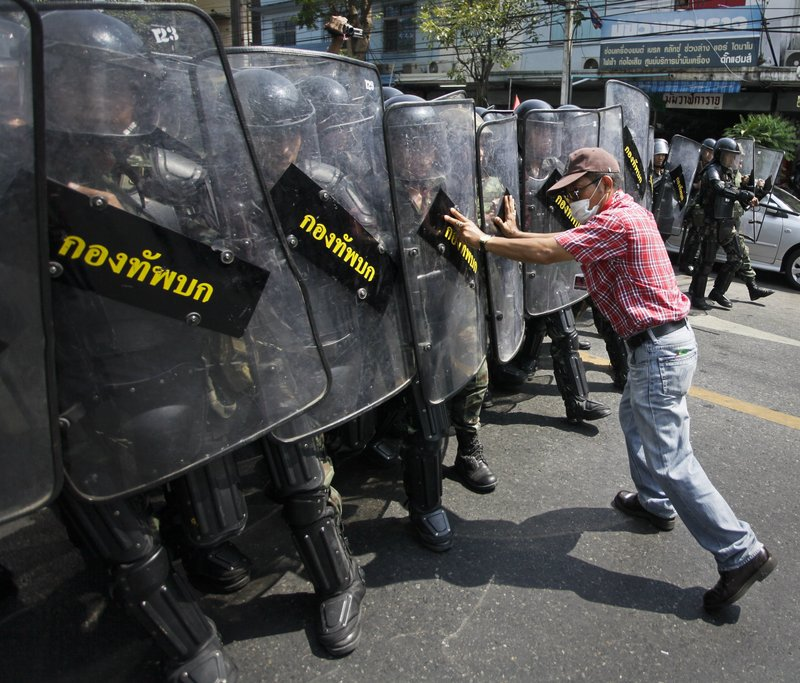 An anti-government demonstrator attempts to hold back an advancing line of Thai soldiers Saturday in Bangkok.