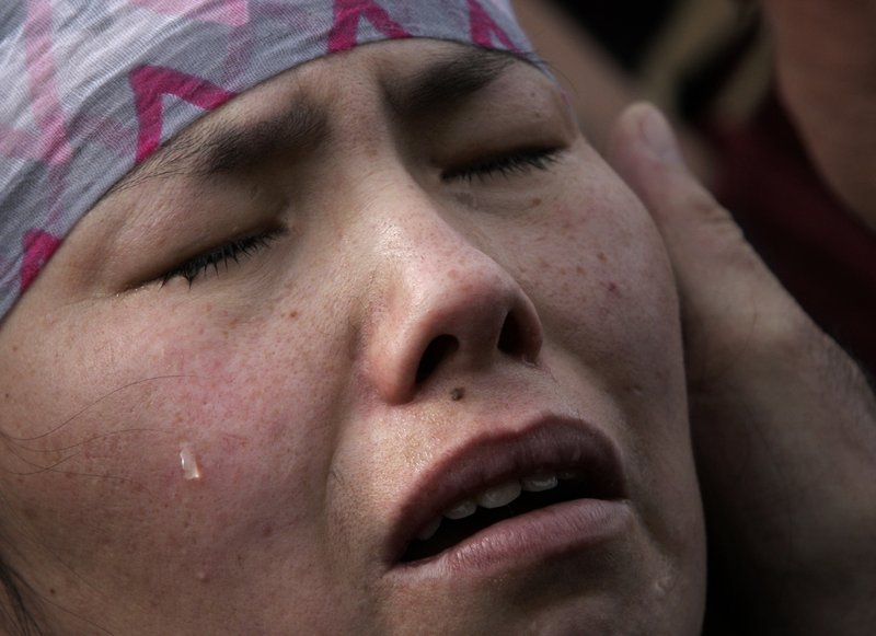 A relative of a victim grieves during a mass funeral at the Ata-Beyit memorial complex on the outskirts of Bishkek, Kyrgyzstan, on Saturday.
