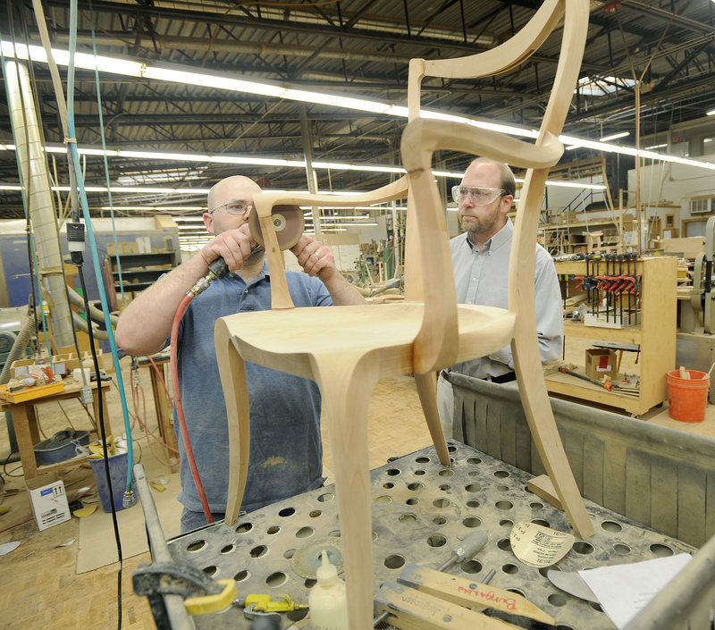 Cabinetmaker George Colby Jr., left, shows reporter Ray Routhier how to sand a chair at Thos. Moser Cabinetmakers. It takes nine to 10 hours to make a chair.