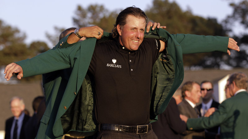 With an assist from former champion Angel Cabrera, Phil Mickelson slips into the traditional winner's green jacket Sunday after completing a three-shot victory with a final-round 67. It was Mickelson's third Masters title.