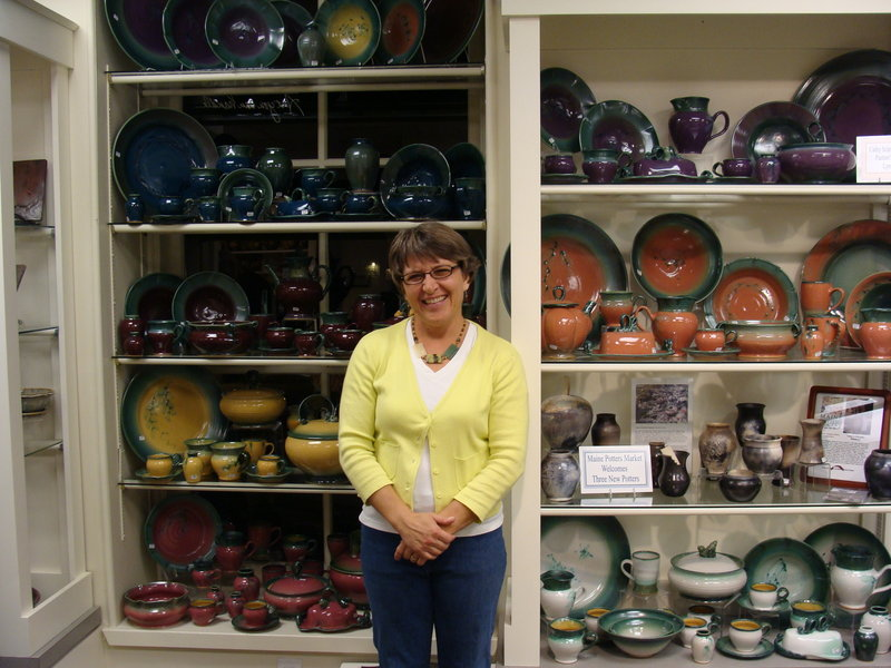 Cathy Schroeder Hammond of Lyman, a potter at the Maine Potters Market in Portland's Old Port, stands in front of her work displayed at the store.