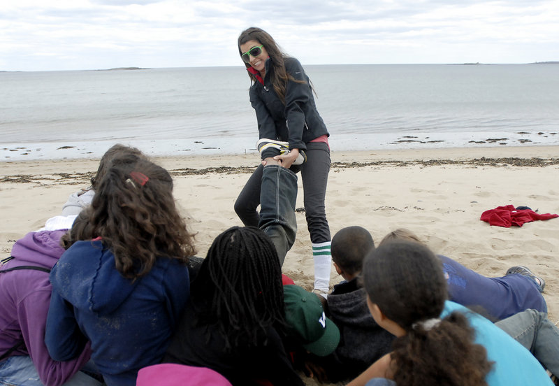 Naturalist Jinx Bauer pulls a student out of a circle to show the effect a wave can have on sea critters.