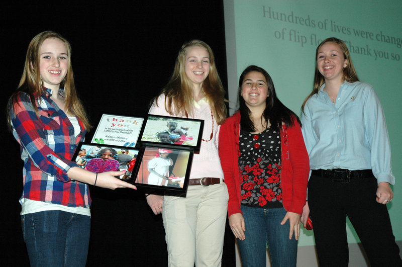 A Flip Flop Challenge to collect and donate 300 pairs of flip-flop sandals for people in the Dominican Republic was held at Thornton Academy Middle School. Grade 7 student Meghan Goebe of Arundel, left, accepts an award on behalf of the student body. The award was presented by TA sophomore Elizabeth Gilboy, second from right, and Cheverus High School students Alison Saunders, second from left, and Katie Saunders, right. The girls delivered the flip-flops to Dominican Republic residents during a mission trip to that country hosted by Saco's United Baptist Church.