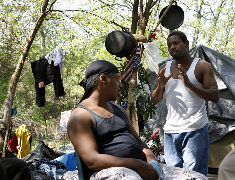 Gino Ortis, left, and fellow Tent City resident Marvin Tomlinson discuss the possibility of leaving the Camden, N.J., camp. Today is the deadline set by the county Board of Social Services to close down the self-governing society of homeless people that's sprung up on a tract of public land.