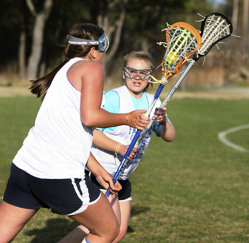 Emma Sipperly, right, defends against Meredith Quirk during a Falmouth girls' lacrosse practice. The popularity of the sport has been on the rise at the school.