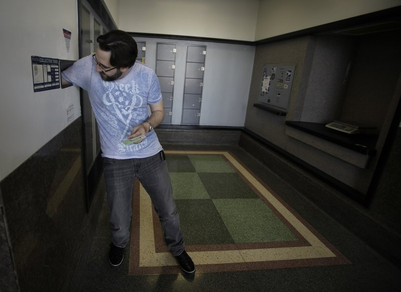 Music producer Alexandre Cardinale sticks his arm inside a mail drop as he mails his tax return forms Wednesday at the Hollywood Station post office in Los Angeles. The average refund this year is about $2,950 – up about $255 over last year.