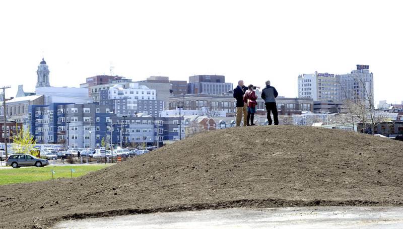 Jim Gooch, Nan Cumming and Mark McAuliffe stand on a berm along a section of the new Bayside Trail, with its great view of the Portland skyline.