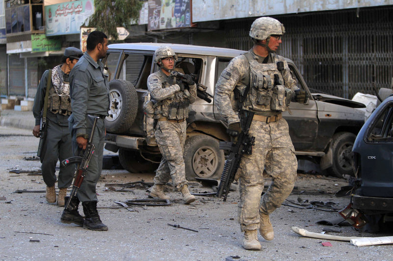 U.S. soldiers arrive at the scene after a car bomb exploded outside a hotel in the southern Afghan city of Kandahar on Thursday. At least a half-dozen people were injured in the blast. Readers wonder why the United States is still involved in this war.