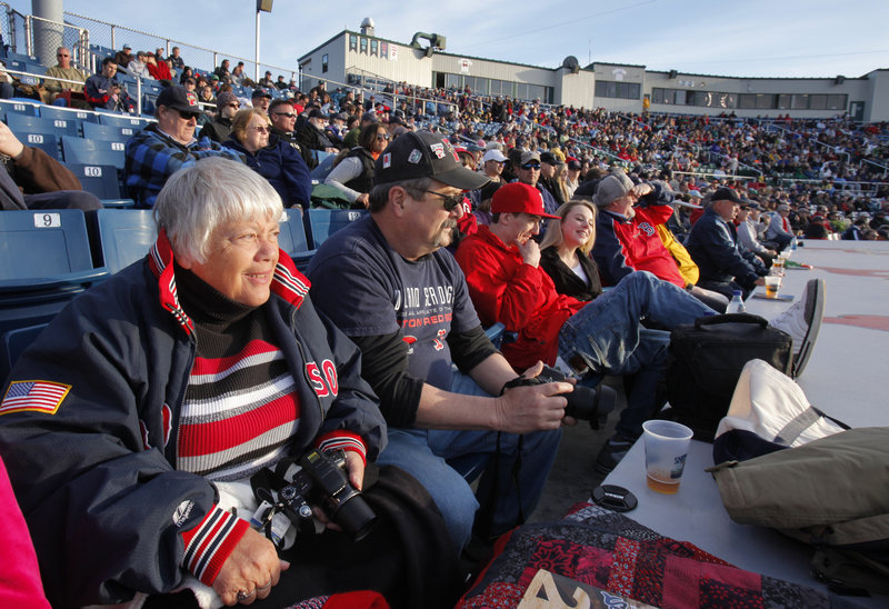 """Jackie Mitchell, left, watches the first inning of the Sea Dogs' home opener Thursday against the Trenton Thunder. Mitchell occupies what she calls the """"best seat in the house,"""" right behind the dugout. The Sea Dogs lost in extra innings, 4-2."""
