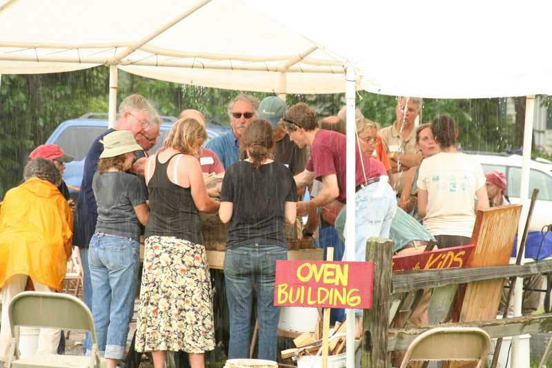 Last year's rain fails to deter participants in an oven-building workshop. This year, there will be two wood-fired oven workshops – one for clay ovens and one for brick ovens.