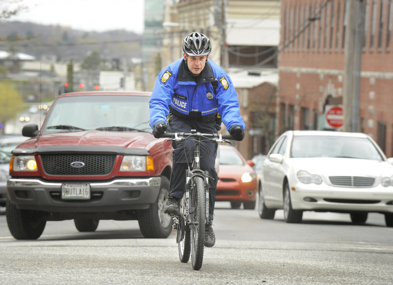 Officer Dan Knight climbs the hill on Preble Street in Portland while patrolling the neighborhood on his bike. Community policing in the city continues to evolve as senior lead officers, such as Knight, are being freed up to focus more on community issues.