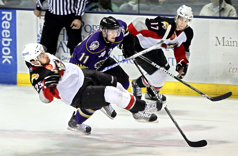 Mark Mancari of the Pirates is upended by Manchester's Trevor Lewis as Marc-Andre Gragnani looks on. Portland will try to pull even in the best-of-seven first-round series when it hosts Game 2 tonight.