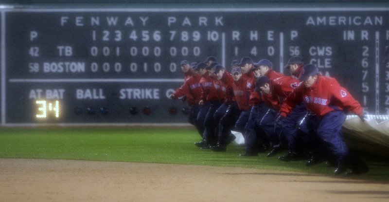 The Fenway Park grounds crew puts the tarp on the field after umpires halted Friday's game because of rain.