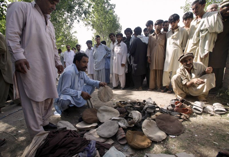 People look at the clothing and shoes of victims at the site of suicide bombing in Kacha Puka, Pakistan on Saturday.