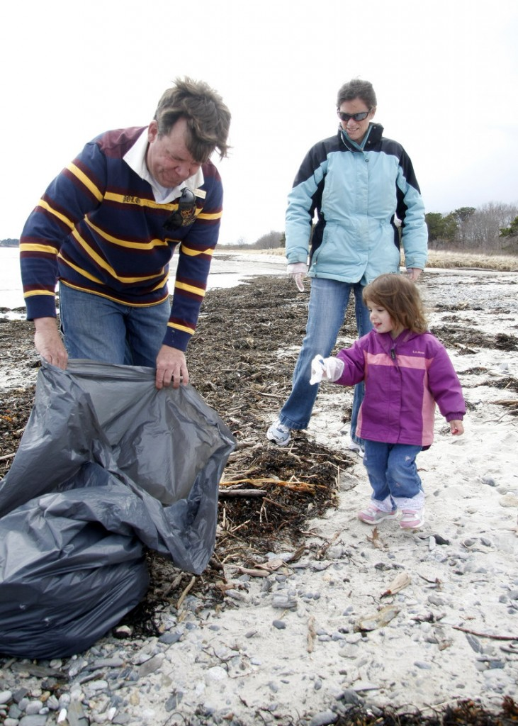 "Derrick Daly, head gardener at the Inn by the Sea in Cape Elizabeth, holds a bag open for Kate Hetrick, 2. She and her mother, Eileen, were among volunteers taking part in the annual cleanup of Crescent Beach on Sunday. ""It's important to teach our kids to be a part of the community and to give back,"" said Kate's mom, of Cape Elizabeth."