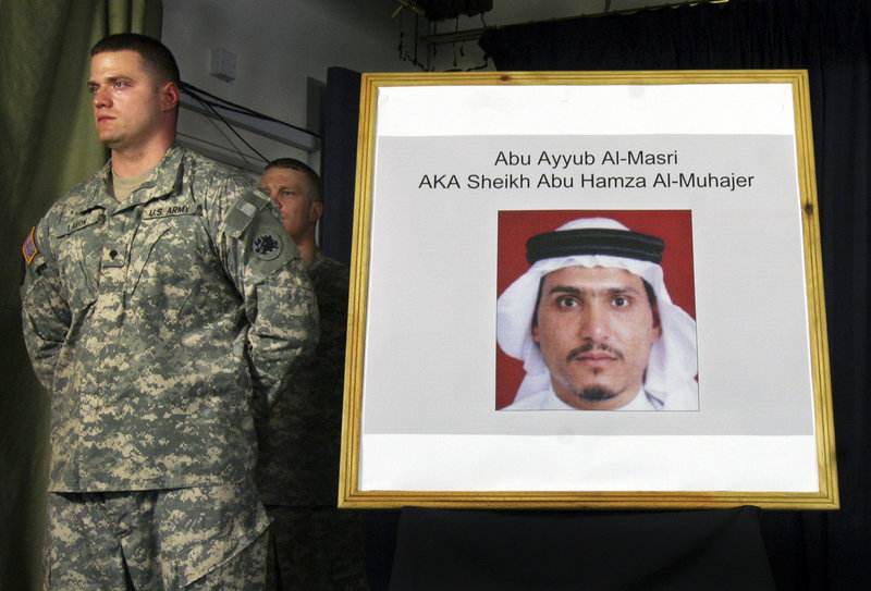 A U.S. soldier stands by a photograph of Abu Ayyub al-Masri, leader of al-Qaida in Iraq, at a news conference in June 2006. Iraq's prime minister said Monday that two of the most wanted al-Qaida in Iraq figures were killed in a joint operation with the United States.