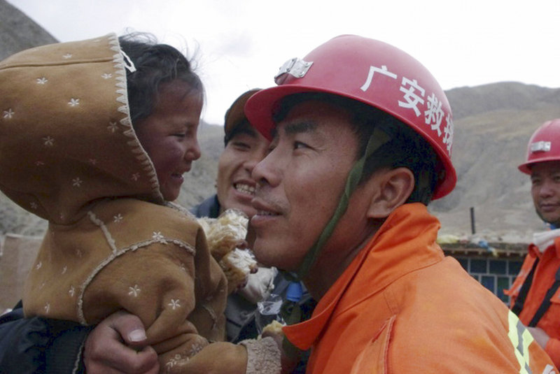 Four-year-old Cairen Baji is hugged by rescue workers Monday after they dug her and an elderly woman from a collapsed mud house near Jiegu, China. The rescue was hailed by state media as a miracle, with footage played repeatedly on television news.