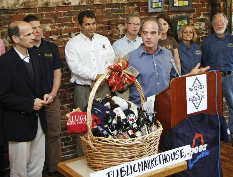 Maine Beer and Beverage Corp. owner Bill Milliken speaks about the shipment of assorted Maine brews, along with other Maine products from the Public Market House, as Gov. John Baldacci listens at left, before sending it off to President Obama on Monday.