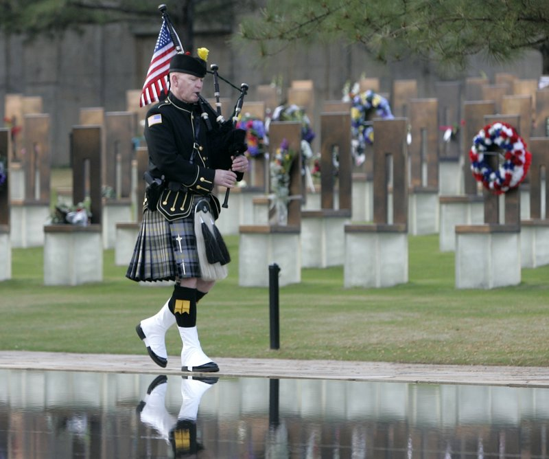 Pipe Sergeant Kevin M. Donnelly, of the DEA Black and Gold Pipes and Drums, walks past the Field of Chairs and the Reflecting Pool at the Oklahoma City National Memorial Monday, starting the ceremony on the 15th anniversary of the Oklahoma City bombing.