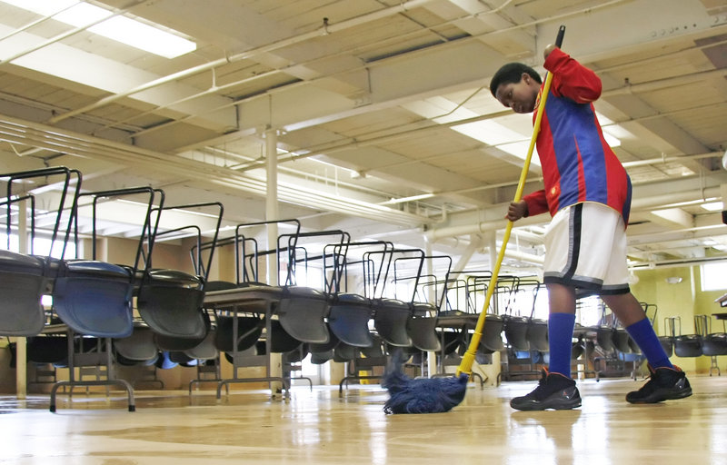 Sahal Hourdeh, a seventh-grader at Lincoln Middle School, mops the cafeteria floor as a student volunteer at Preble Street Resource Center. Students in the program will also go to Cow Island, to engage in gardening and environmental projects aimed at building leadership skills.
