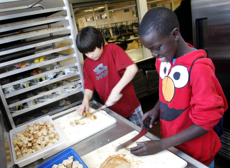 Lincoln Middle School seventh-graders David Mathew, right, and Jordan Sparks cube bread to be used for croutons in the kitchen at Preble Street Resource Center.