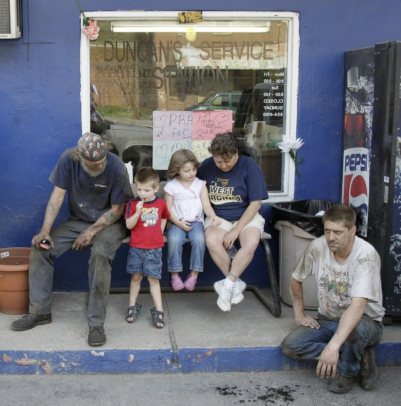 From left, Jerry Bearfield, Jaden Clemons, 3, his sister Gabrielle, 4, their grandmother Gladys Clemons and Jerry's brother Randy Bearfield gather in Whitesville, W.Va., April 12 for a national moment of silence for the 29 miners who died in the explosion at Massey Energy Co.'s Upper Big Branch mine in Montcoal, W.Va., on April 5. Critics say the industry is full of former government officials, leading to federal regulations that benefit the companies at the expense of worker safety.