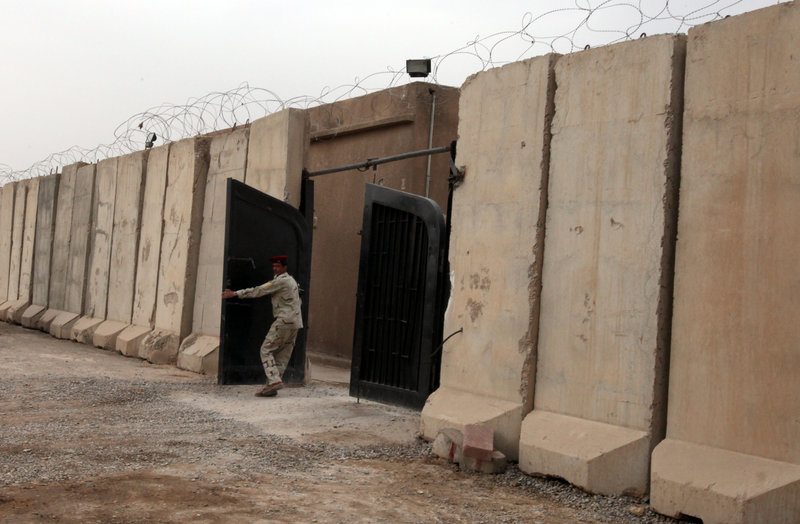 An Iraqi soldier closes the gate to a Baghdad prison. Iraqi officials say they are investigating claims that detainees, mostly Sunnis, were tortured at a prison in Baghdad.