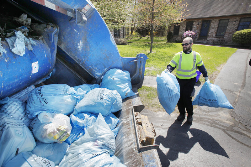 Jerry Mains throws a trash bag into the back of a garbage truck on Coachlight Lane in Portland Thursday. City Manager Joe Gray has suggested raising the fee for pay-per-bag trash bags.