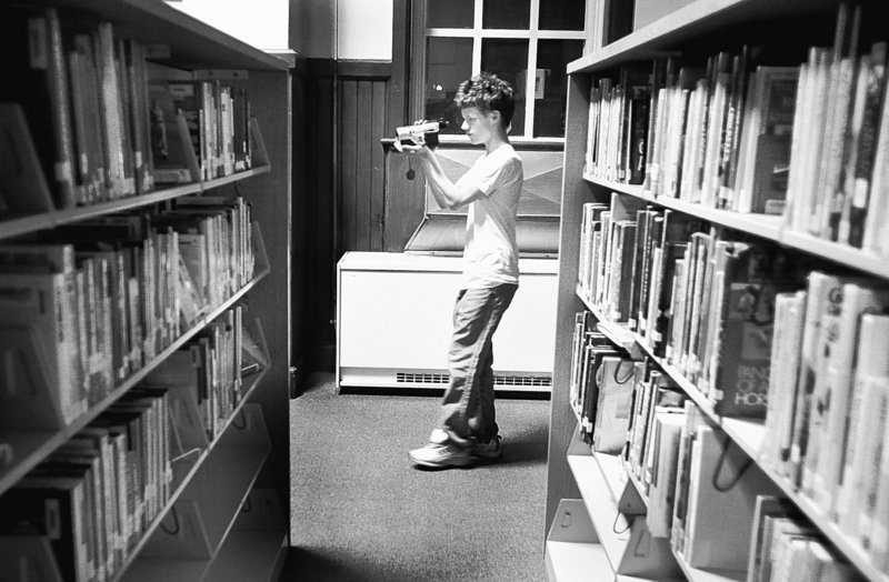 Student Dylan Sargent, 18, films Kara Marston, out of view, as she asks questions and hopes for a paranormal response in the Portland High library. The school has long been rumored to be haunted by restless spirits.