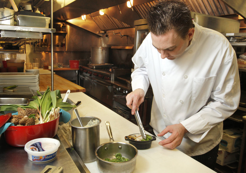 Jeffrey Savage, executive chef at On the Marsh Bistro in Kennebunk, arranges fiddleheads in his Spring Peekytoe Crab Bake appetizer.