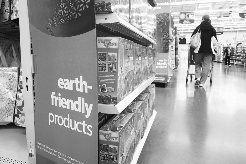 A Walmart customer walks past a line of earth friendly products.