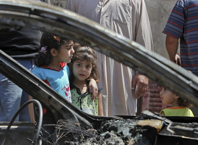 Zahra Naaim, 4, center, and Balqes Youssif, 6, left, stand next to a destroyed vehicle in the Shiite stronghold of Sadr City in Baghdad, Iraq, on Saturday, a day after bombings killed 69.
