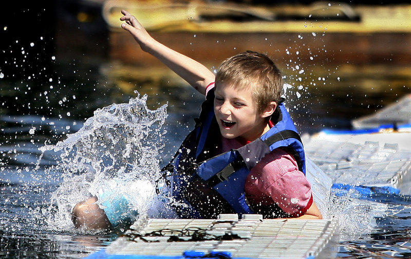 Chris Hamlet, 7, falls into the water after making it across 17 crates during the lobster crate-running competition at the Fishermen's Festival in Boothbay Harbor on Saturday. Competitors demonstrated their agility by running across 40 crates tied to a dock and a boat.