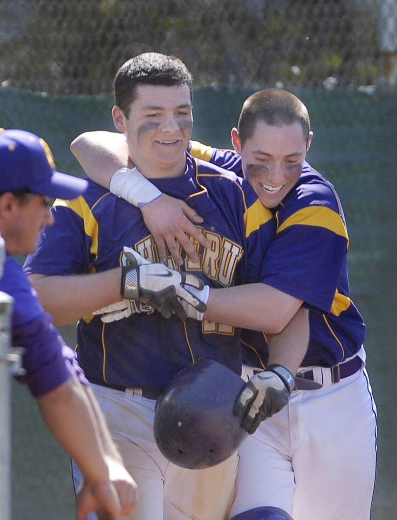 Peter Potthoff of Cheverus, left, is welcomed by teammate Nic Lops after scoring the winning run on a passed ball in the seventh Saturday, producing a 5-4 victory that ended Deering's 50-game winning streak.