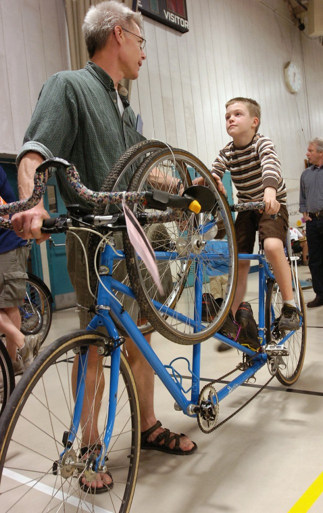 David Waggoner and his son Sam, 7, of Gorham, wait in line to purchase a tandem bike.