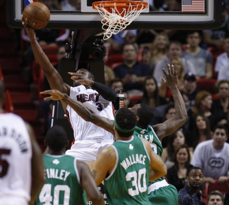 Dwyane Wade of the Miami Heat slips inside against Boston's Michael Finley, left, Rasheed Wallace and Tony Allen for a reverse layup Sunday, two of his 46 points in Miami's 101-92 playoff win.