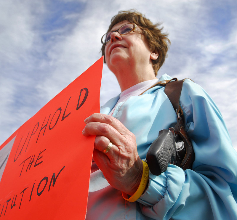 "Mary Lou Bagley, 63, of Portland carries a .38-caliber Smith & Wesson and holds a sign reading ""Uphold the Constitution"" at Back Cove in Portland during an open-carry gathering Sunday."