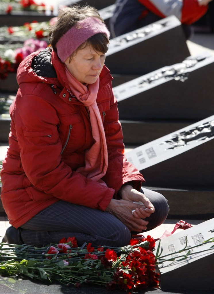 A relative of Klavdia Luzganova, who died when a reactor at the Chernobyl nuclear plant exploded on April 26, 1986, mourns over her grave Monday at Mitino cemetery in Moscow. Health groups estimate that radiation from the explosion has caused more than 700,000 premature deaths.
