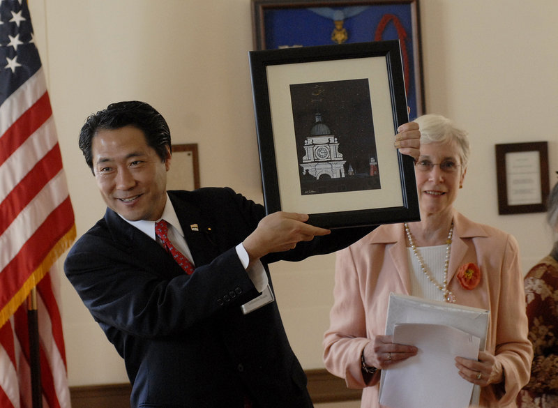 Takenobu Honda, chairman of the Shinagawa Assembly, shows off a painting of Portland's City Hall presented to his city. Watching is former Portland Mayor Ann Pringle.