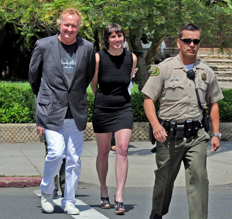 Actor Randy Quaid and his wife, Evi, are escorted into court Monday in Santa Barbara, Calif. They were arrested on outstanding warrants.