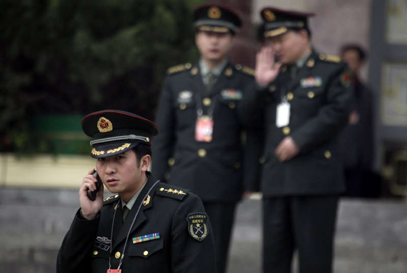 """A Chinese military officer uses his mobile phone outside the Great Hall of the People in Beijing. China is about to pass a law requiring telecom companies and Internet service providers to report discussions of """"state secrets,"""" but critics say the law is aimed at stifling dissent by political activists."""