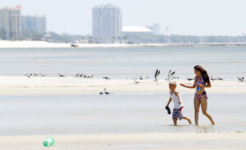 Damien Theriot, 6, left, and his mother Rachel Hebert, both of New Orleans, La., enjoy the pristine white sands of the beach in Gulfport, Miss., on Tuesday.
