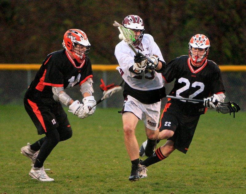 Austin Spencer of Greely, center, heads down the field Tuesday night between Dylan Seeley, left, and Tim Millett of North Yarmouth Academy during NYA's 10-7 victory. Each team has a 1-1 record in boys' lacrosse.