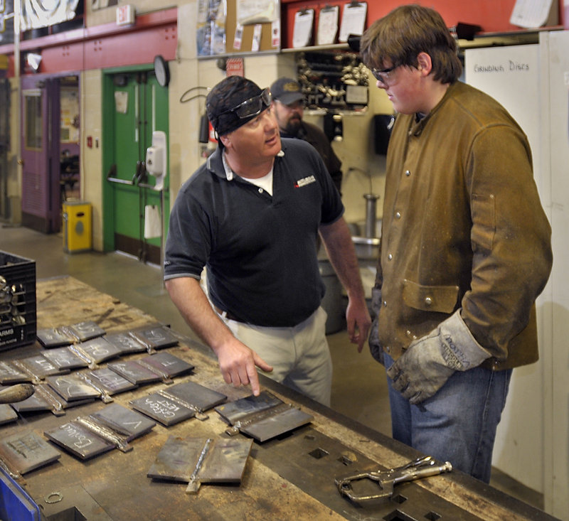Teacher Bill Presby talks with Ben Martin of Limington concerning his welding test.